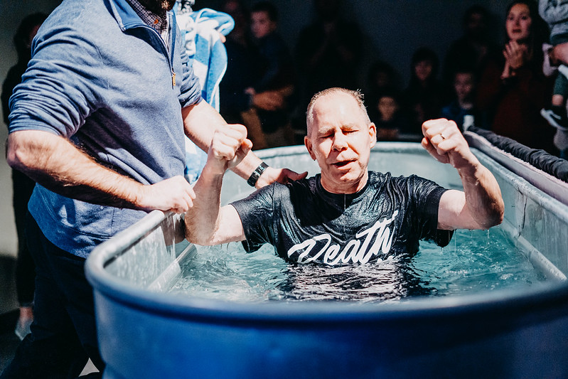 Man getting baptized at Mercy Hill Church, water tank, pastor